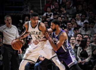 Dos jugadores de la NBA de diferentes equipos luchan por el balón en la cancha.