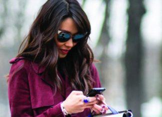 Mujer con abrigo y bolso usando su teléfono inteligente Android.
