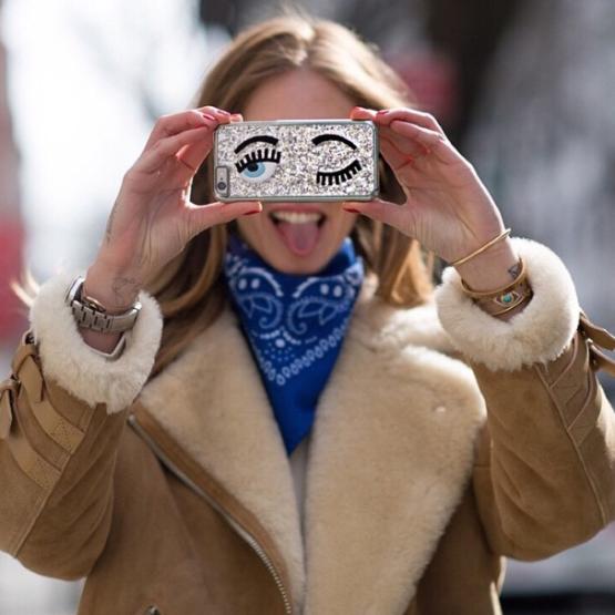 Chica sosteniendo un iPhone a la altura de sus ojos, pues su carcasa tiene un par de ojos pintados.