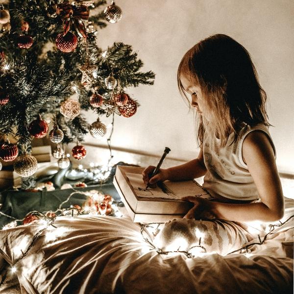 Niña escribiendo carta a Santa Claus árbol de Navidad