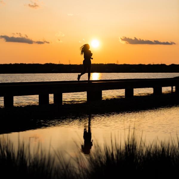 Mujer corriendo ejercicio atardecer muelle
