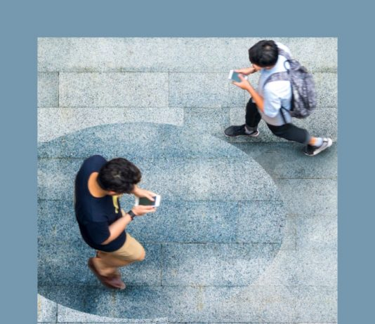 jovenes mirando el celular mientras caminan